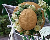 Straw hat with wreath of white dahlias and clematis