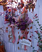 Autumn flowers on garden fence with 'Welcome' sign