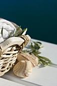 Handtücher und Olivenzweige im Korb, daneben Steine