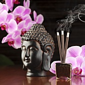 Buddha head, orchids and incense sticks