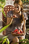 Woman with peaches on garden chair