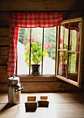 Milk can & wooden moulds in front of window in Alpine chalet