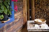 Selbstgemachte Bauernbutter auf Holztisch vor einer Almhütte