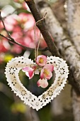 A metal heart and japonica hanging on a tree