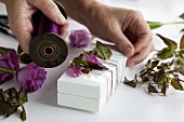 Decorating a gift box with lisianthus and twine
