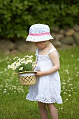 A little girl holding a straw hat filled with daisies