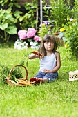 A little girl sitting on a lawn with carrots