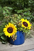 Sunflowers and sprigs of blackberries in an enamel pot