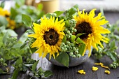 Sunflowers and blueberry sprigs in a ceramic bowl
