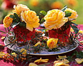 Yellow roses with sea buckthorn on plate with sand