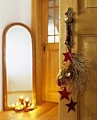 Door handle decorated with felt stars and Euphorbia twigs