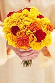 Hände halten Strauss aus gelben Rosen