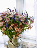 Arrangement of astrantia and veronica in old milk can