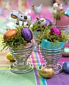 Eggcups with coloured egg shells, moss and chocolate eggs