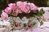 Romantische Jardiniere mit Rosengesteck und Efeuranken