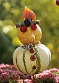 Little man made from ornamental gourds, rose hips, heather