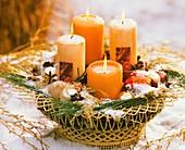 Adventlich dekorierter Drahtkorb mit vier Kerzen