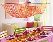 Sommerlich gedeckter Tisch mit kleinen Blumensträußen