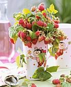 Raspberries used as cut flowers in vase with ladybird motif