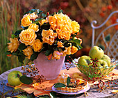 An arrangement of yellow roses, rose hips and apple quinces