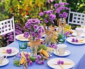 Tisch gedeckt mit Glattblattaster, Mais, Weizen und Weintrauben
