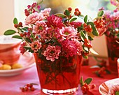 Chrysanthemums and cotoneaster in vase