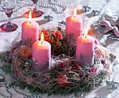 Kranz aus Tannenzweigen und rosa Kerzen