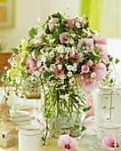 Vase of mallow flowers and gypsophila