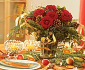 Arrangement of red roses, cones and ivy on Advent table