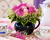 Phlox, gypsophila & hosta leaves in jug on table laid for coffee