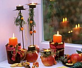 Winter decoration with apples, cinnamon sticks & candles