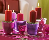 Candles with fir needles in pink and purple glasses