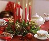 Advent wreath in green and red on Christmassy tea table