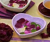 Table decoration of rose petals in a heart-shaped bowl