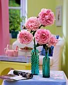 Peonies (Paeonia) on turquoise bottles
