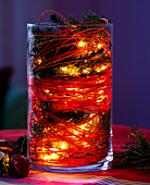 Glass with pine sprigs, cane and fairy lights
