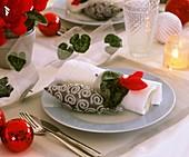 Gedeck mit rotem Alpenveilchen und Baumschmuck dekoriert