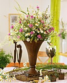 Iron vase of meadow flowers, marguerites, knapweed & grasses