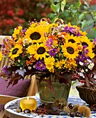 Autumn arrangement of sunflowers, Michaelmas daisies, rose hips