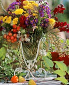 Vase of chrysanthemums, Michaelmas daisies & ornamental apples