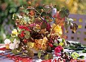 Autumn arrangement: bowl with florist's foam, roses, rose hips