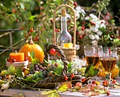 Autumn decoration: basket of vines, leaves, candles, wineglasses