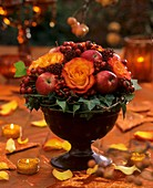Roses, rose hips, ivy, Skimmia and medlar in a bowl