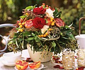 Autumn arrangement of roses, pomegranates and dates