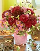 Arrangement of chrysanthemums, Michaelmas daisies and ivy