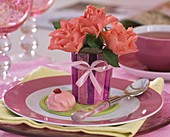 Three salmon-pink roses in a glass