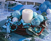 Candle surrounded by dogwood wreath with blue tree ornaments