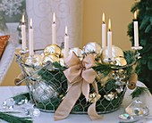 Christmas baubles, candles and greenery in wire basket