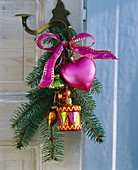 Spruce branch with tree ornaments on a door handle