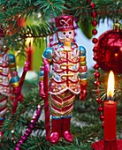 Nutcracker and burning candle on Christmas tree